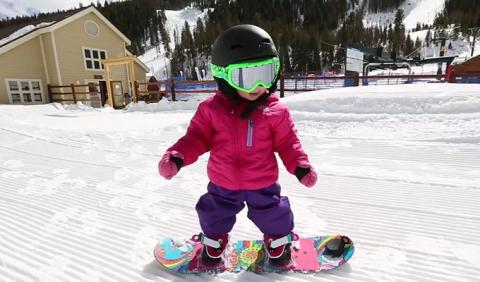Little kid learning to snowboard in Michigan